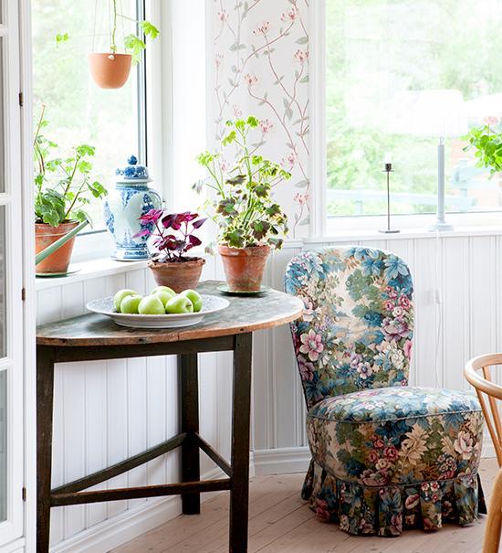 Fåtölj och sidobord i matrummet. Den blå urnan är köpt på second hand och det grå fatet är från Mateus. Hängkrukan i terrakotta är från Ethelhems krukmakeri på Gotland.