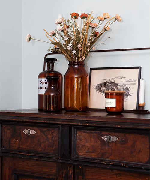 Gamla glasburkar samsas på en stor byrå i vardagsrummet. En bukett pappersblommor fungerar som evighetsblommor. Doftljus från H&M home.