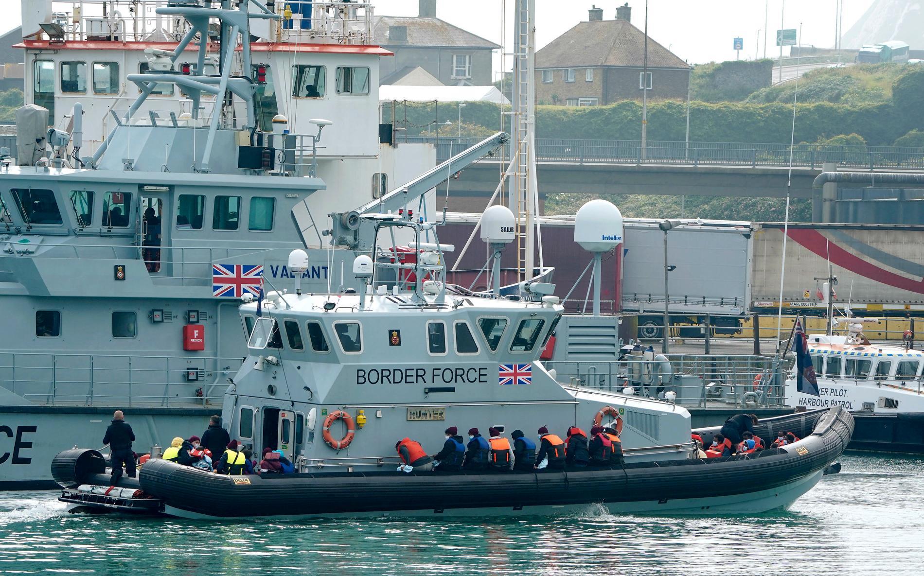 En grupp migranter förs in till hamn av den brittiska kustbevakningen. Arkivbild