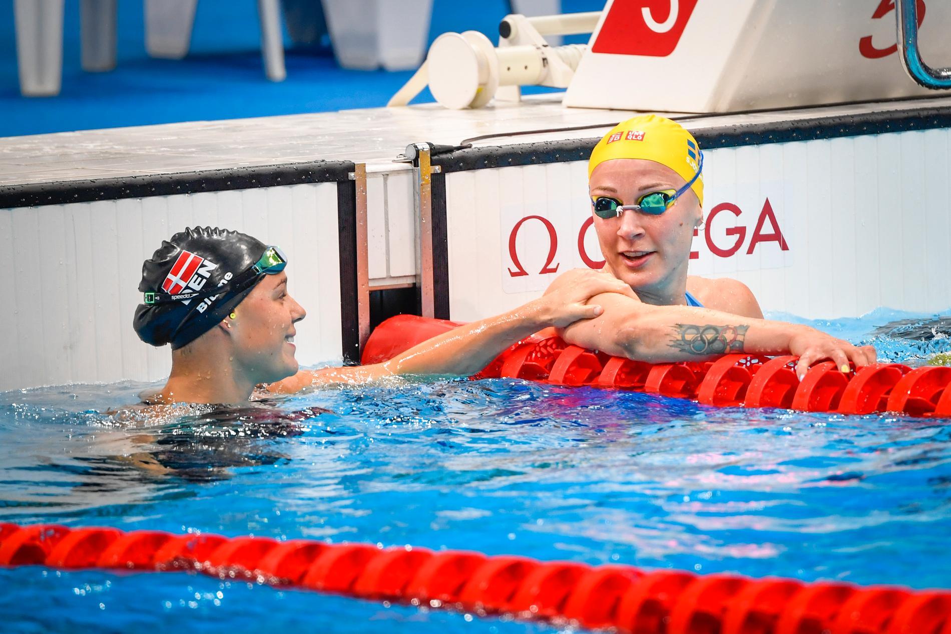 Regerande OS-mästaren Pernille Blume, segrare i semifinalheatet, ger tvåan Sarah Sjöström en vänskaplig klapp efter målgången.