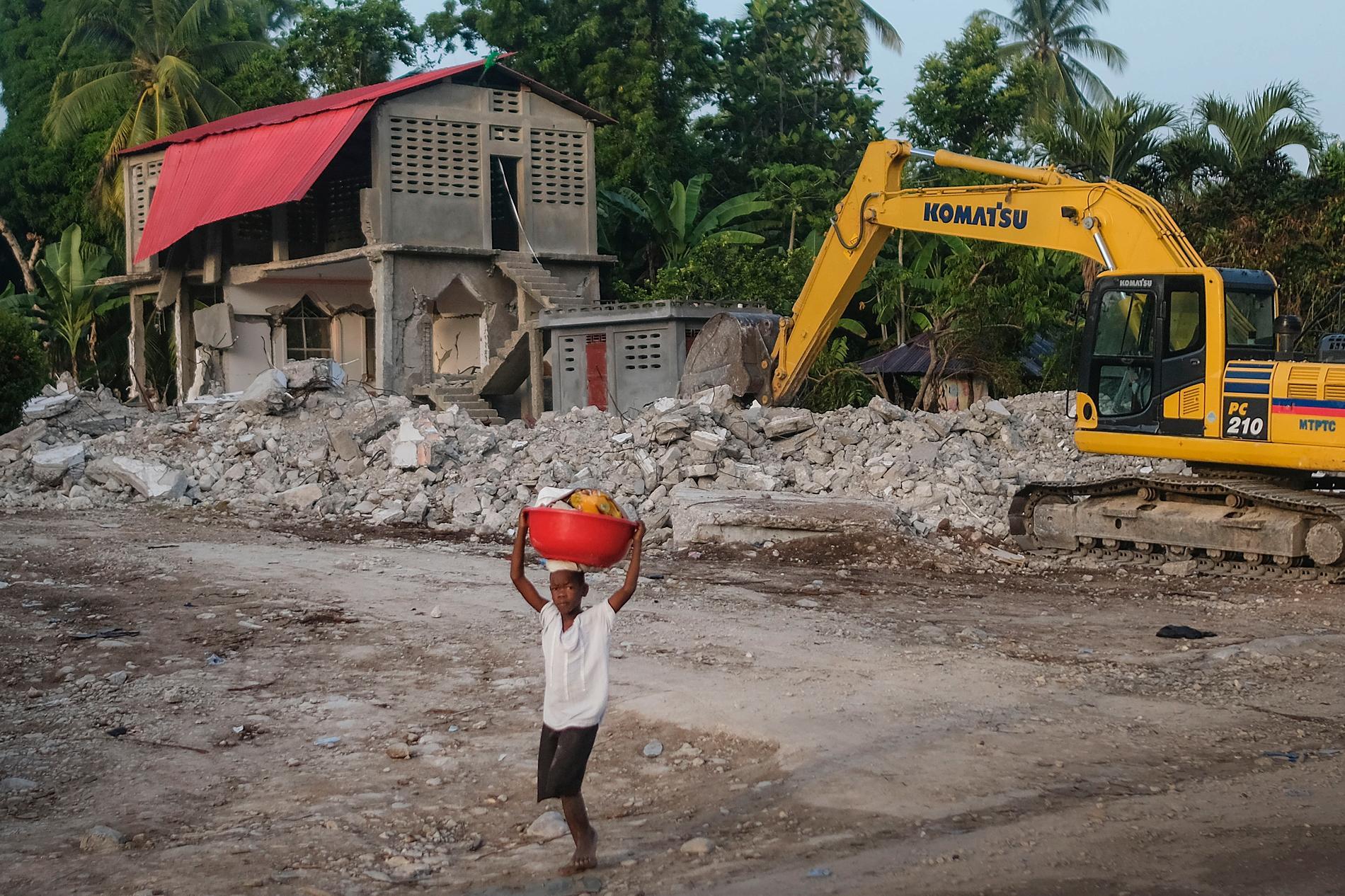 En pojke passerar en kyrka i Maniche, sydvästra Haiti, som förstörts i jordskalvet.