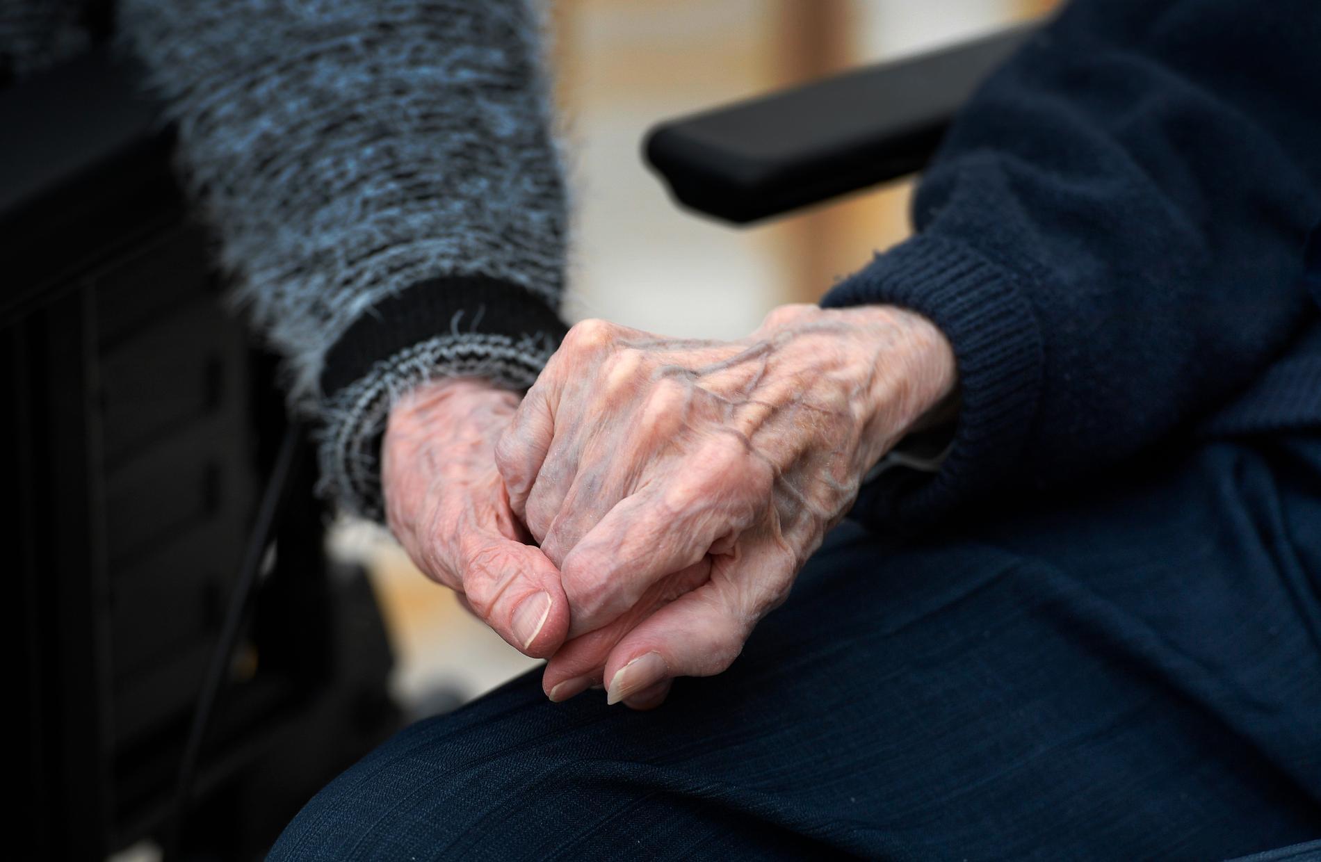 Två personer håller varandra i handen på äldreboende.