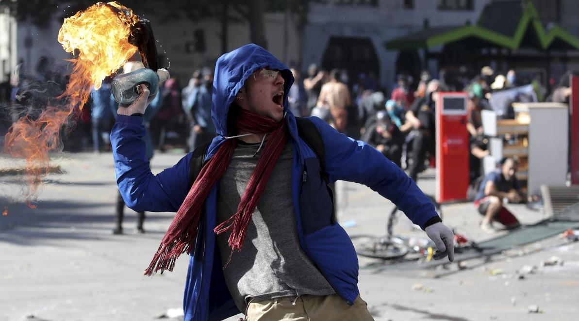 En demonstrant kastar en brandbomb mot polisen under en demonstration med studenter och fackföreningar.