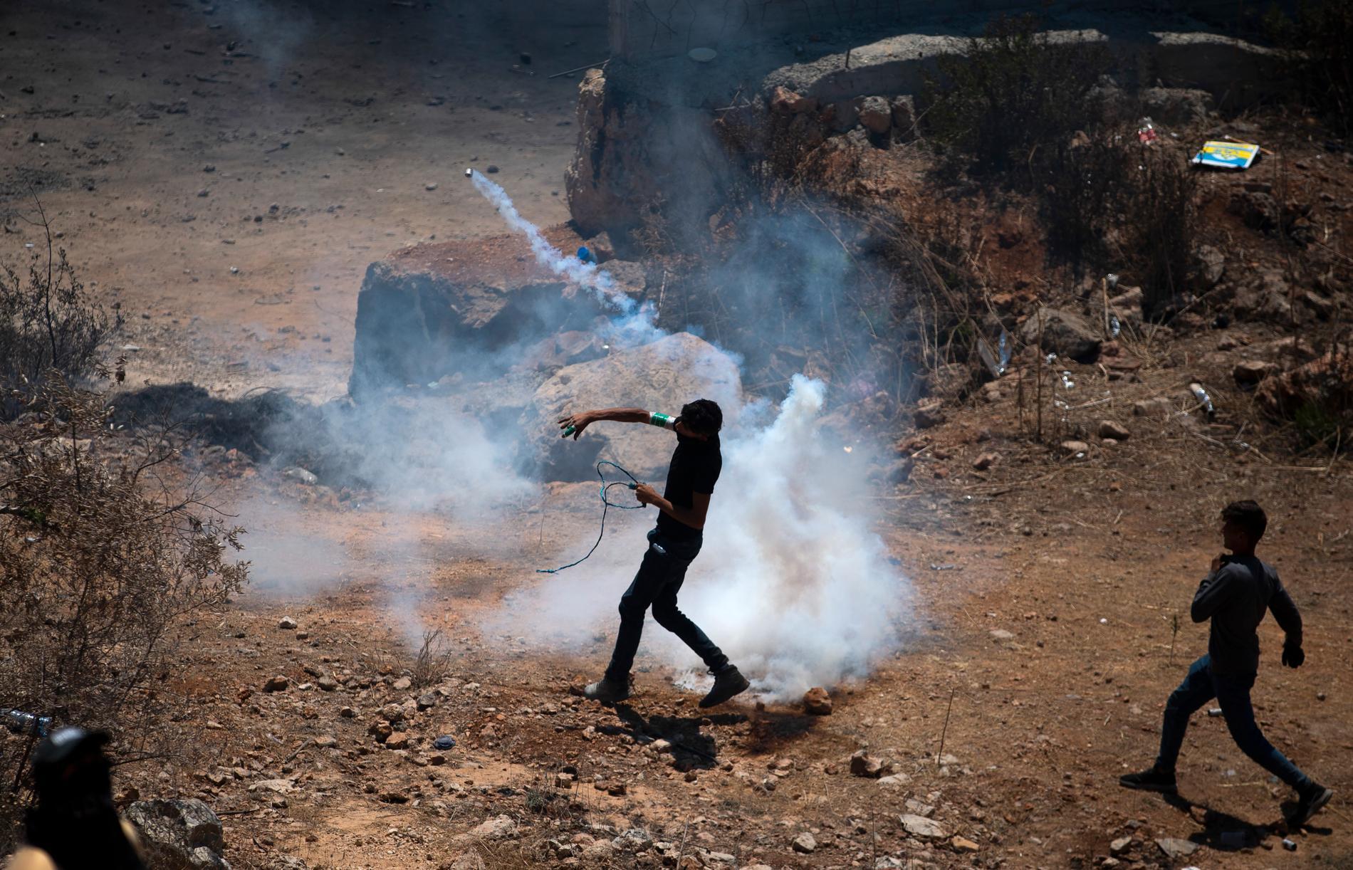 En palestinsk demonstrant kastar tillbaka en tårgasbehållare som israelisk militär använt vid protester mot bosättningen i Eviatar. Bild från tidigare i juli.