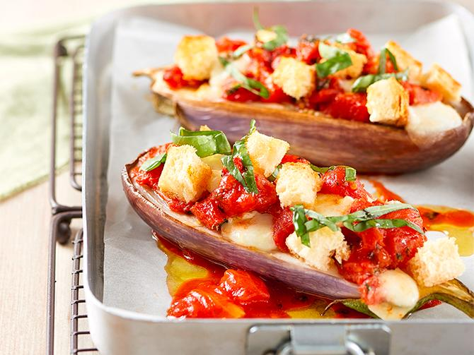 Auberginehalvor med tomater och knaprigt bröd.