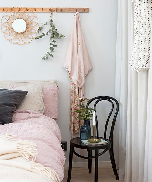 Sovrummet med en ljusgrå fondvägg har identiska grå gardinlängder som i huvudrummet, vilket binder samman rummen på ett fint sätt. Sängen är bäddad med rosa linnelakan från Mio. Ovanför sängen en trälist med hängare från H&M home där bland annat en spegel från Indiska hänger.
