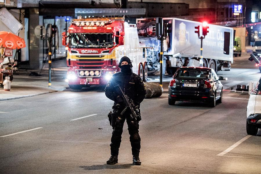 En polis vaktar medan lastbilen bärgas från attentatsplatsen på fredagkvällen.