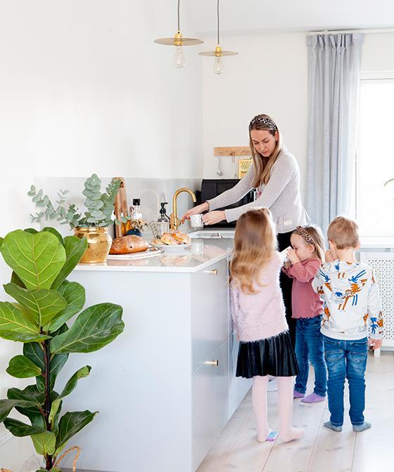Hanna och barnen Thilde, Elsa och Charlie. Köksluckorna är Veddinge från Ikea med mässingsknoppar från Beslag design. Kran från Tapwell och gröna växten är en fiolfikus. Lampor från Frama, köpta på rum21.