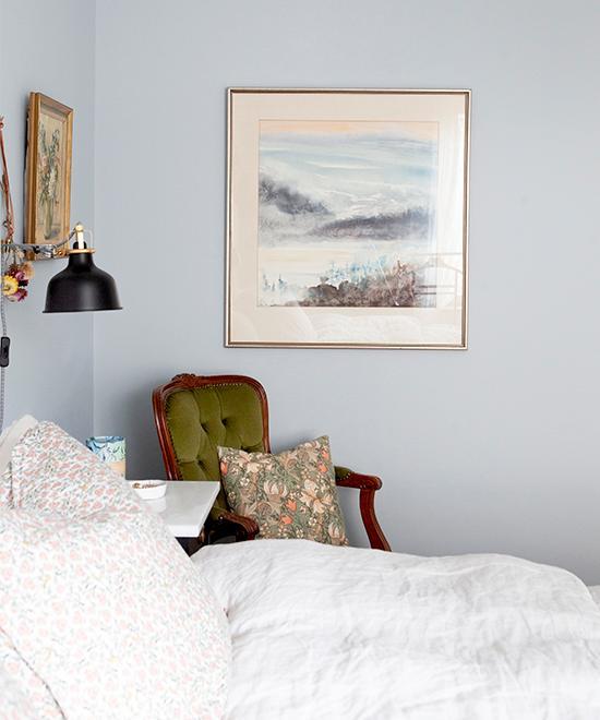 Vilsamt inrett i parets sovrum. Tavlan är en akvarellmålning Hanna ärvt efter sin farmor. Den gröna karmstolen är köpt på loppis, i den ligger en kudde som Hanna sytt av William Morris tyg, också köpt på loppis. Lampa från Ikea.