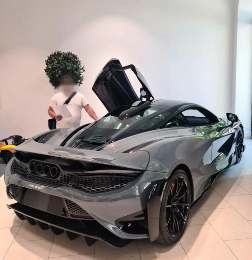 """Här poserar John framför en lyxbil av märket McLaren som han påstår sig ha köpt. Men """"John"""" står i själva verket inte registrerad som ägare av några som helst fordon."""