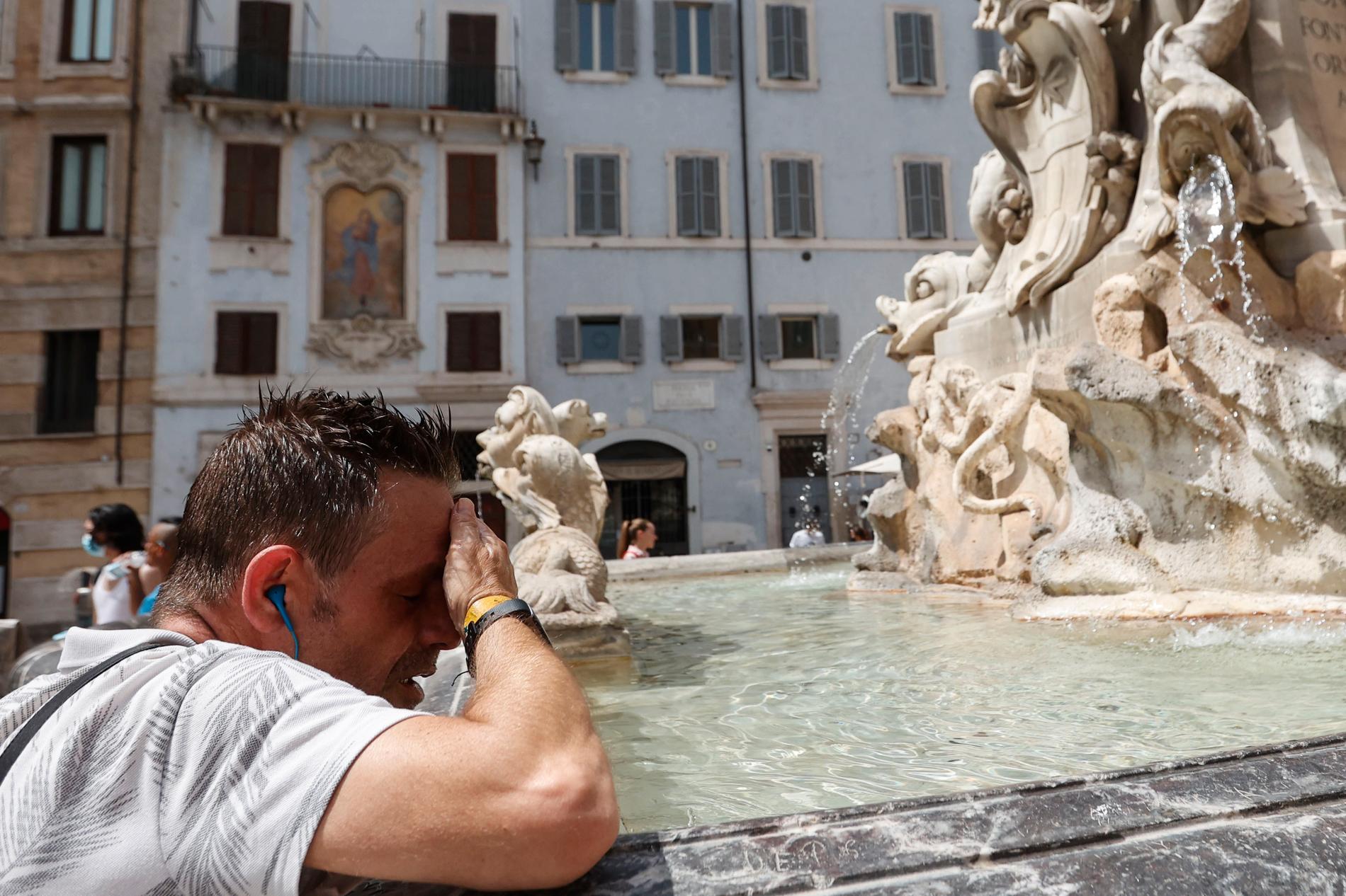 En man försöker svalka sig i hettan i Rom.