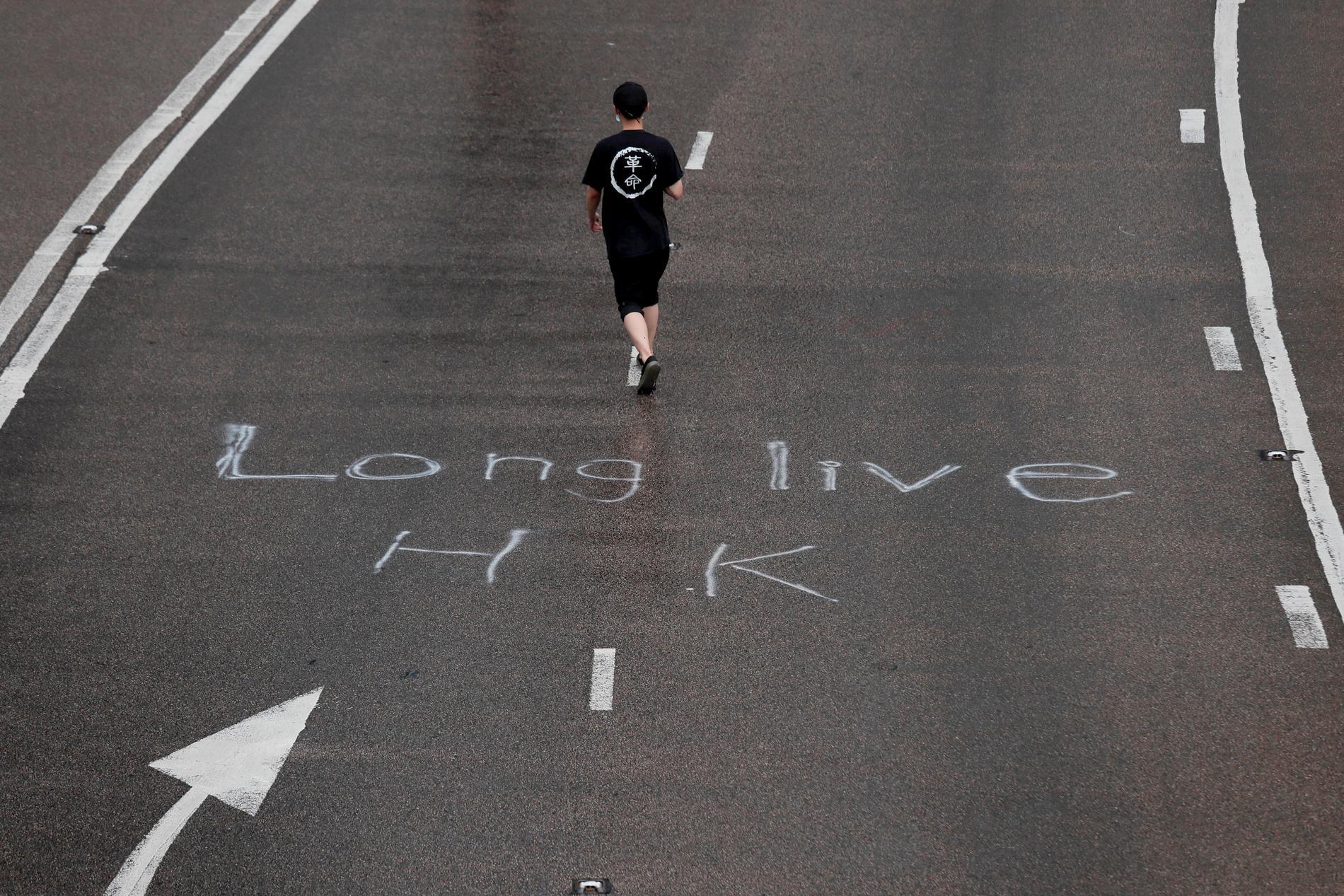 """En demonstrant passerar över orden """"Länge leve HK"""" som spraymålats på vägen."""
