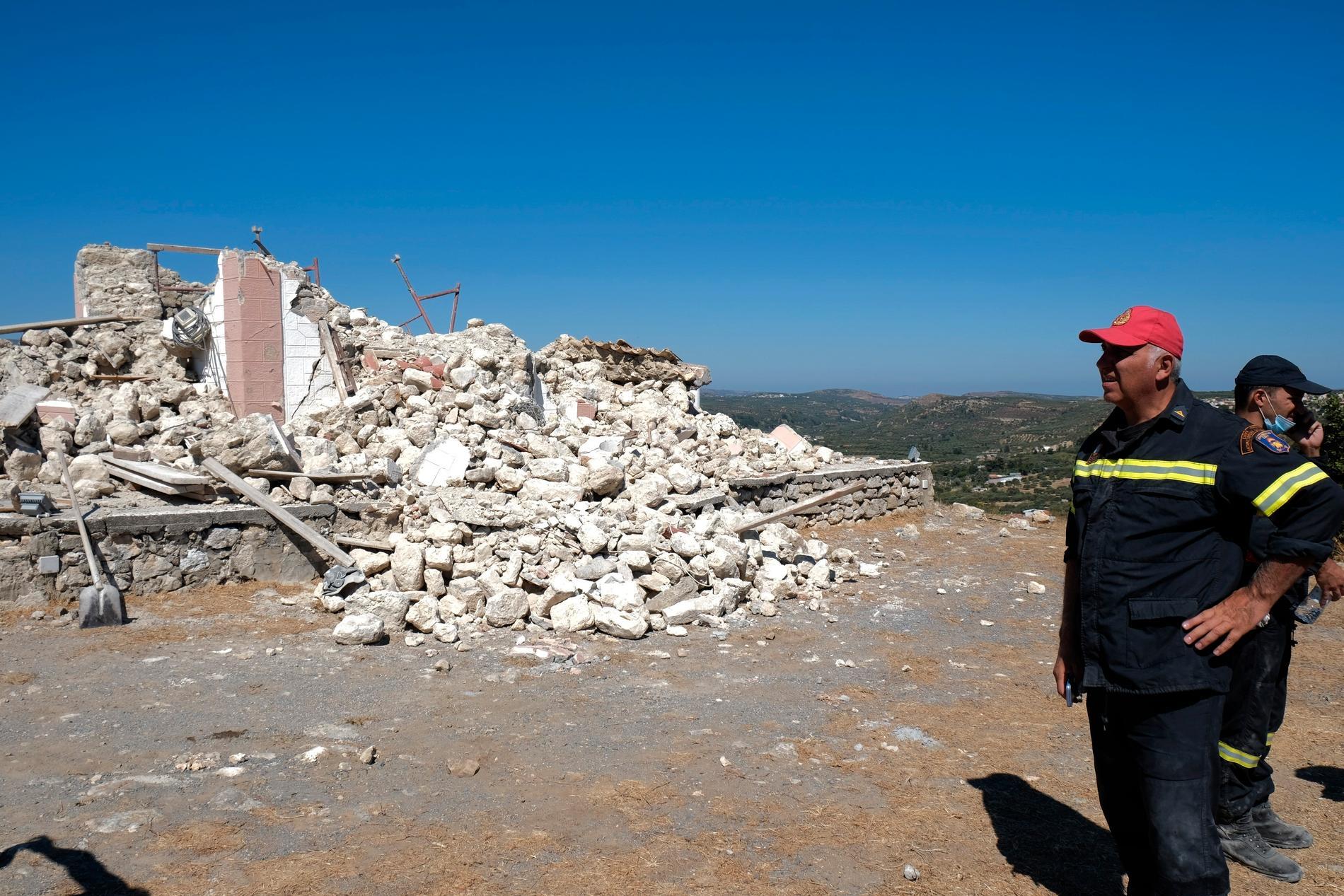 Räddningspersonal bredvid en förstörd kyrka i byn Arkalochori.