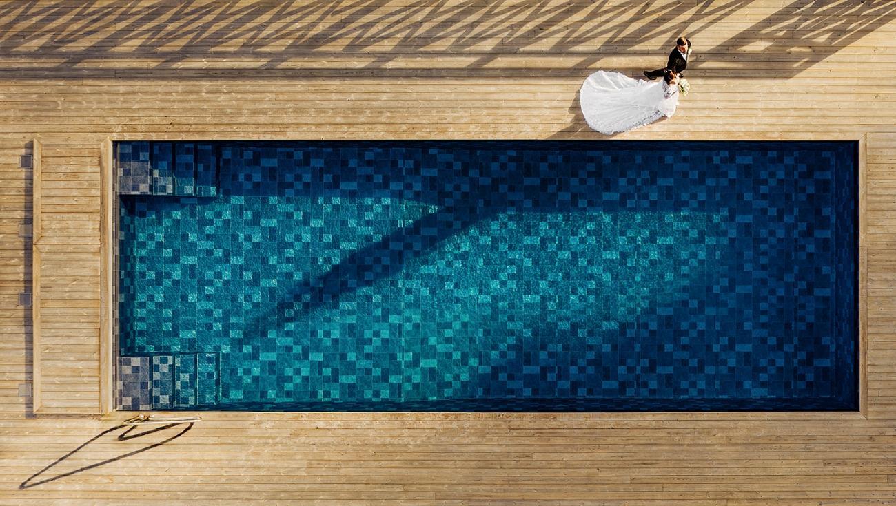 """""""Bröllopsparet gick runt den blå poolen mot receptionen, där gästerna väntade. Det var en varm sommarsolnedgång. Jag tog fotot när deras långa skuggor pekade mot poolräcket, vilket skapade ett skuggformat hjärta. En pool av kärlek."""""""