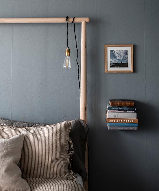 På väggen hänger ett egentaget fotografi från en semester i Halmstad. En osynlig hylla som gömmer sig mellan böckerna agerar sänghylla.