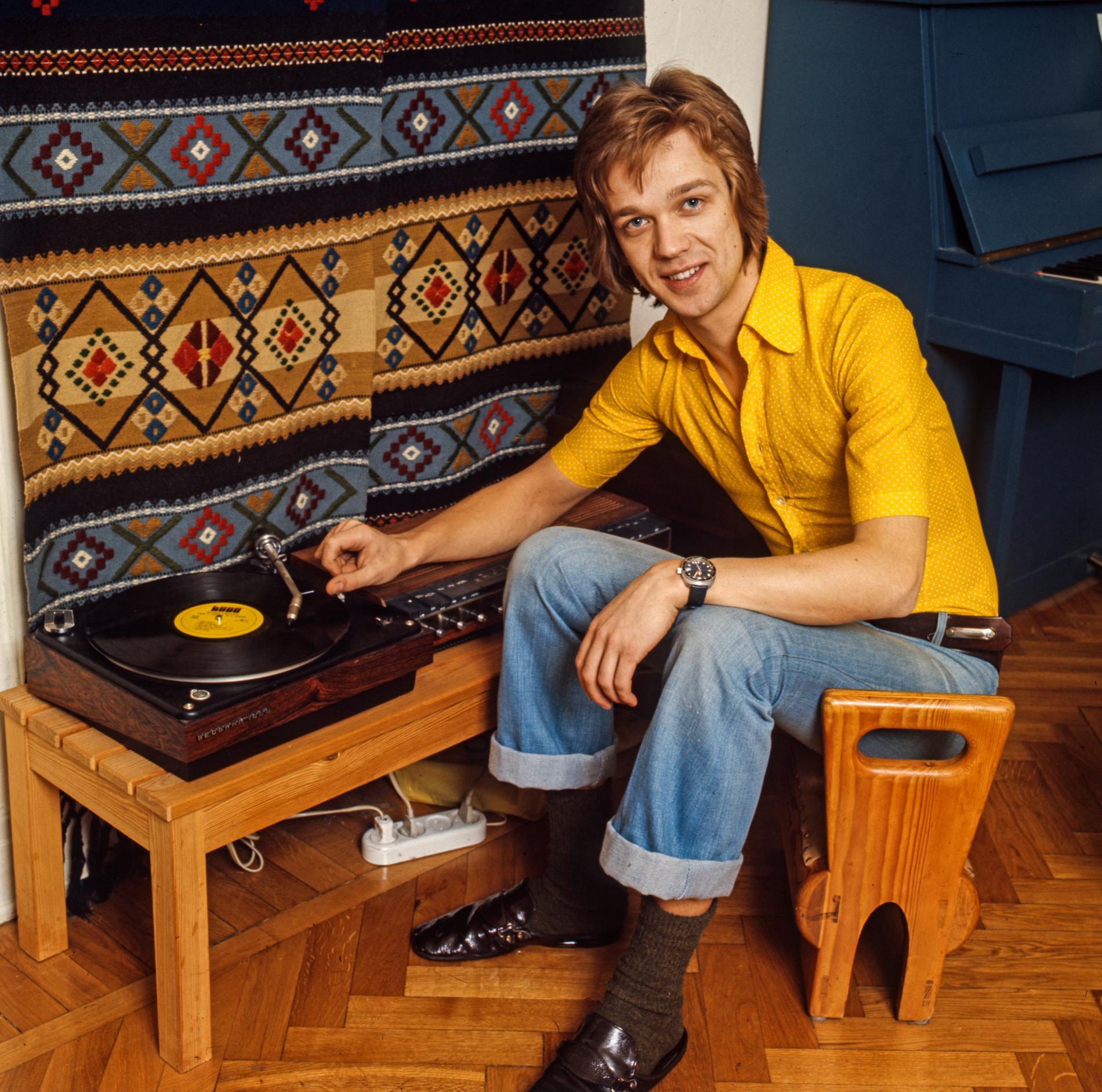Björn Skifs sitter på en pall på parkettgolvet och spelar en vinylplatta på en grammofon hemma i vardagsrummet i Stockholm 1973.