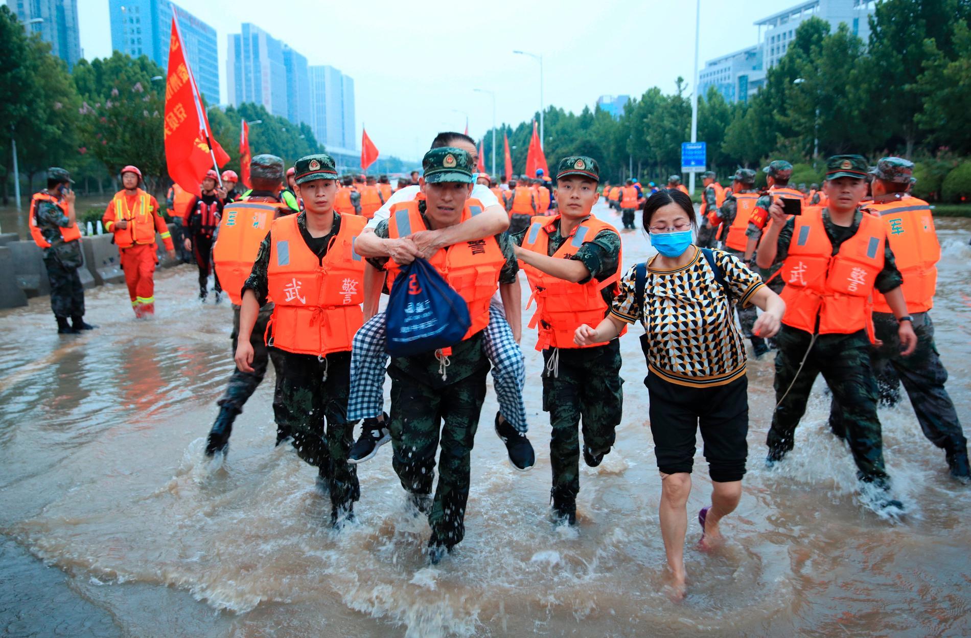Kinesisk militär evakuerar invånare i samband med översvämningarna i staden Zhengzhou.