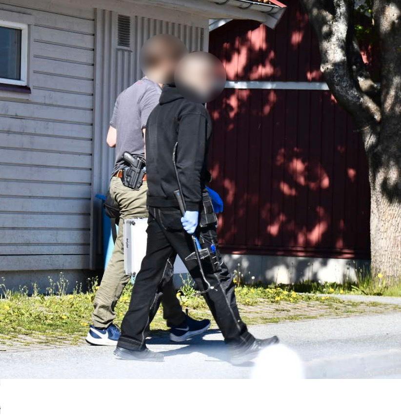 Här lämnar poliser en adress norr om Stockholm efter att ha brutit sig in i en lägenhet som en rappare kopplas till. Tillslaget med kofötter skedde i en samordnad insats.