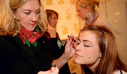 Susanne Thorson, 26, och Anna Magnusson, 25 i bakgrunden medan Amelia Widell, 22, får hjälp med eyelinern av reporten Kicki Norman.