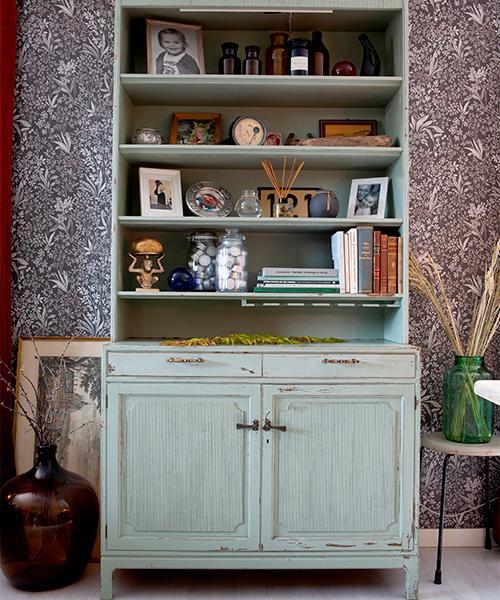 I vardagsrummet står ett stort vackert vintageskåp som Kristin fick i byte mot ett annat skåp. Hon valde att behålla den lite avskavda färgen. Den stora glasflaskan är köpt på loppis och passar perfekt att ha kvistar i.