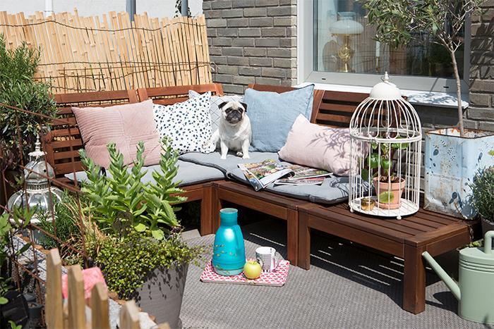 Sommartid används terrassen flitigt; med dörren öppen, suddas gränsen mellan ute och inne bort och känslan av ett eget hus förstärks. Terrassens hörnsoffa, skapad av Ikeas loungeset, har Joy gjort inbjudande och bekväm med hjälp av dynor och kuddar i olika färger och mönster. Mycket grönt i olika krukor samt ljuslyktor skapar extra trivsel. Hunden Sally ligger gärna och solar sig i soffan.