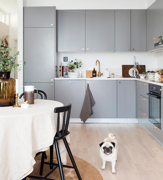 Kökets fasta inredning i vinkel, med släta skåpsluckor och låd - fronter i grått och med marmor på bänkskivorna, ingick i lägenhetens utrustning. Elegant, strikt och tid - löst. De vitvaxade trägolven fanns också på plats från början. Joy tycker att det är ett väl fungerande kök med gott om förvaringsut - rymmen. Hunden Sally håller med.
