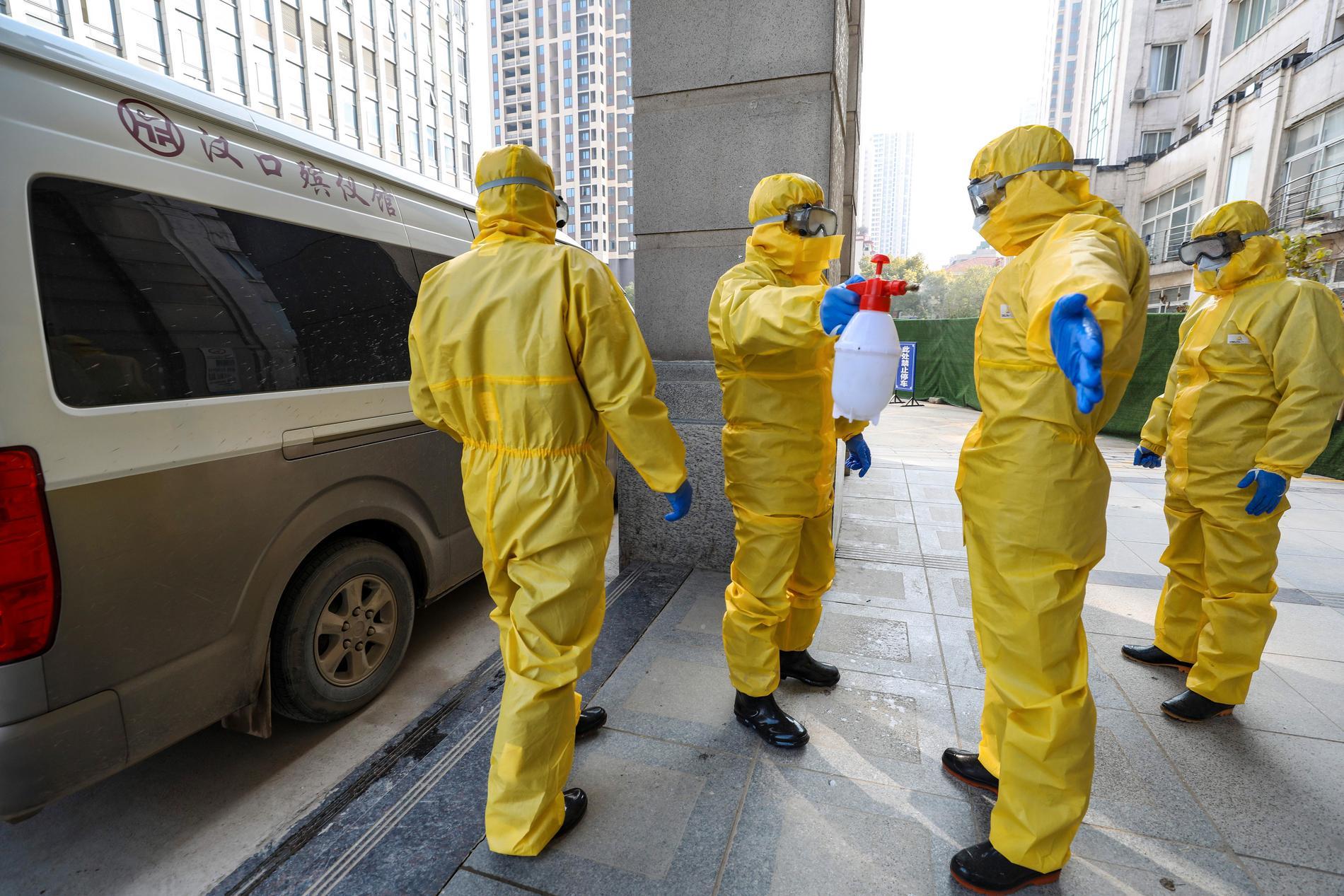 Begravningspersonal desinficerar sig efter att ha hanterat ett virusoffer i Wuhan.