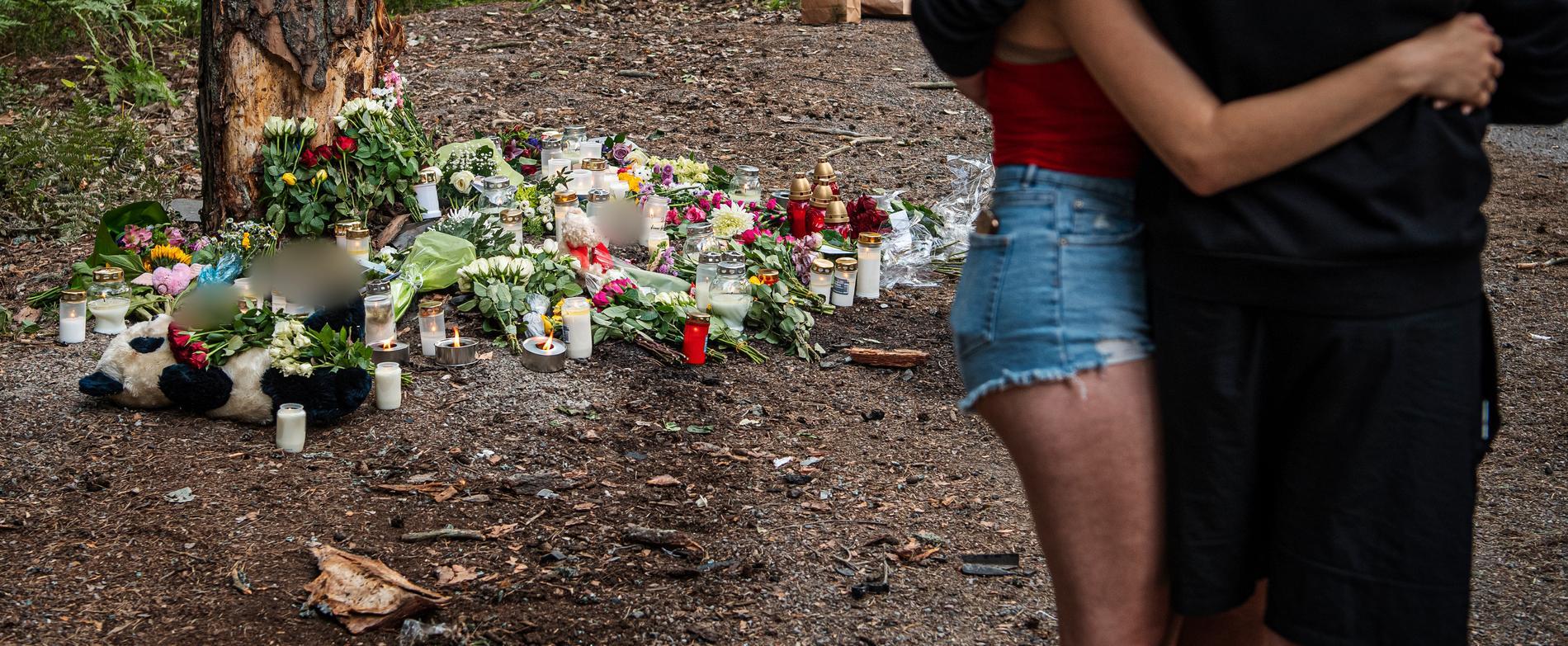 Blommor och ljus på en minnesplats för kvinnan som dog.
