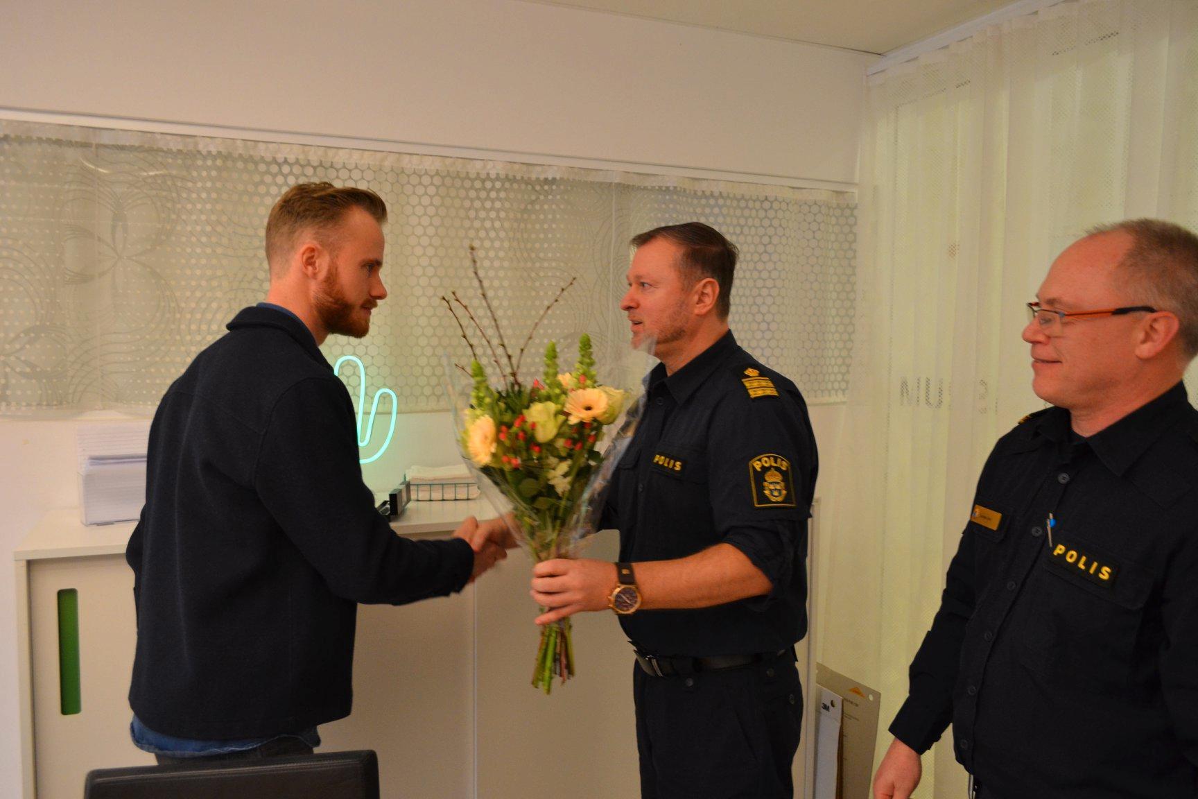 Jakob Gelberg tar emot blommor från biträdande polischef Daniel LIndberg och förundersökningsledare Magnus Lörd.