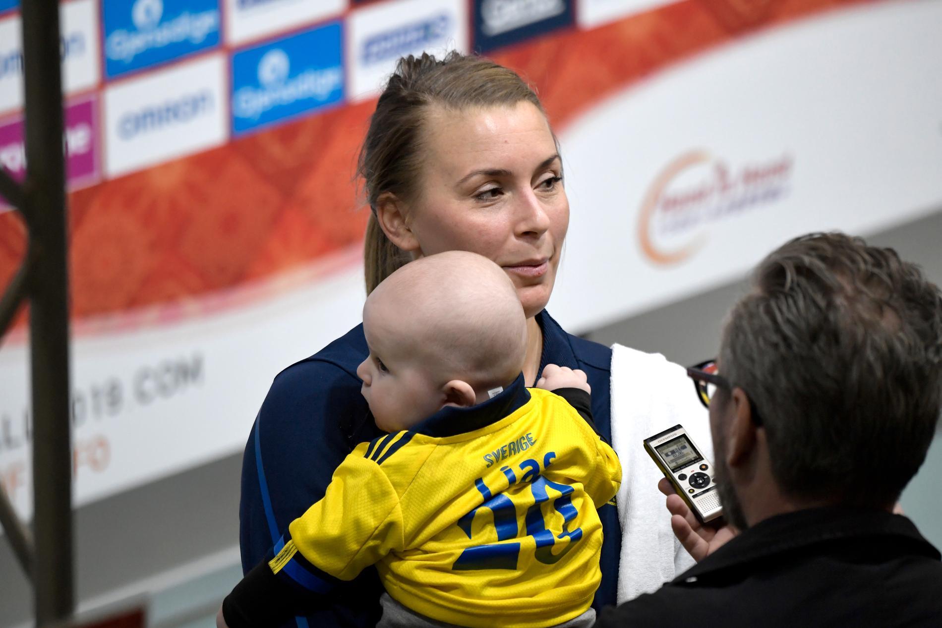 Sveriges Isabella Gulldén med sin son i mixade zonen efter segern i matchen mellan Sverige och Japan under handbolls-VM 2019.