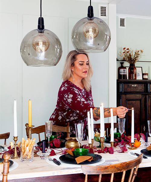 Dukat för festmåltid. Kristin tänder ljusen i matsalen. Mässingsljusstakarna är mestadels fyndade på loppis. Bordet är dekorerat med kvistar från den egna trädgården.