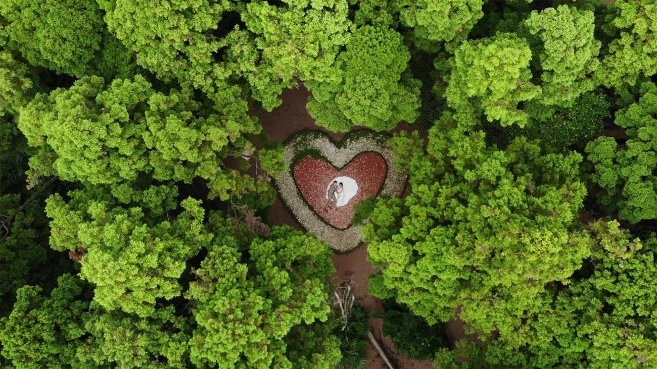 """""""Detta är ett bröllopsfoto taget av ett par på en välkänd naturskön plats i Taiwan som kallas skogens hjärta. Det är nästan en måste-se attraktion för alla par. Från en höghöjdsvinkel finns det en hög med kärleksfulla stenar i skogen som symboliserar parets eviga bad."""""""