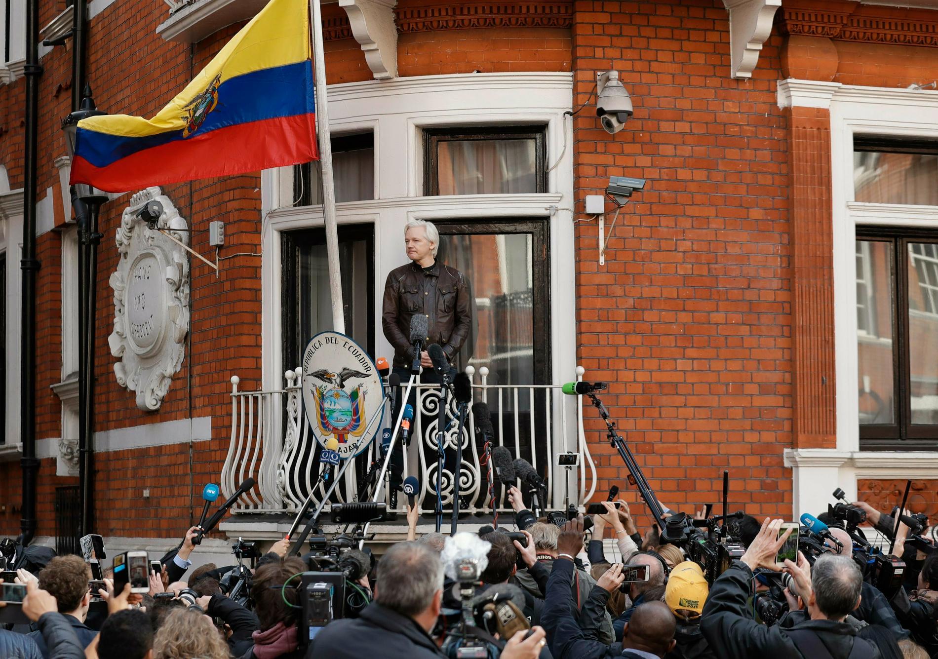 Julian Assange tittar ut från balkongen från Equadors ambassad i London 2017.