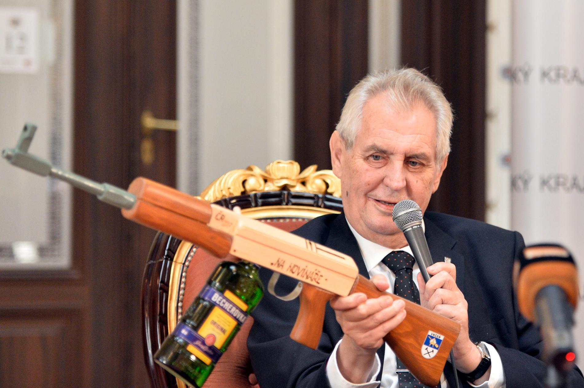 Tjeckiens president Milos Zeman viftar med en AK-47:a på presskonferensen