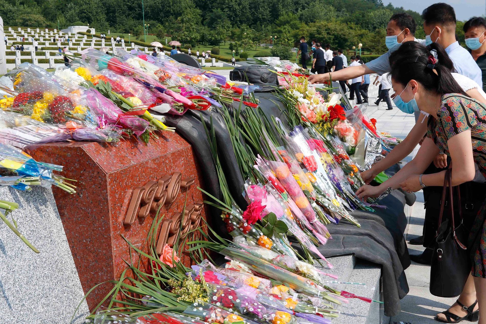 Nordkoreaner lägger blombuketter vid en krigskyrkogård i huvudstaden Pyongyang, på årsdagen av vapenstilleståndsavtalet med Sydkorea 1953.