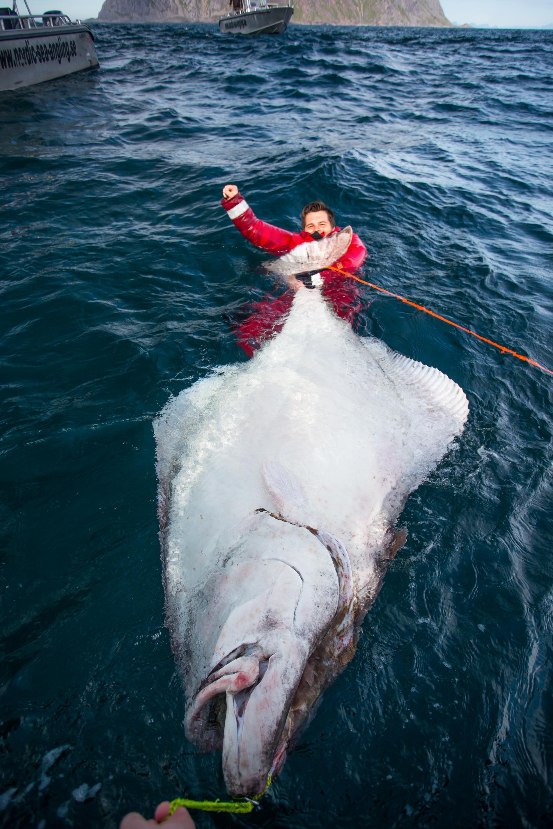 En av fiskarna visar upp jättefångsten.