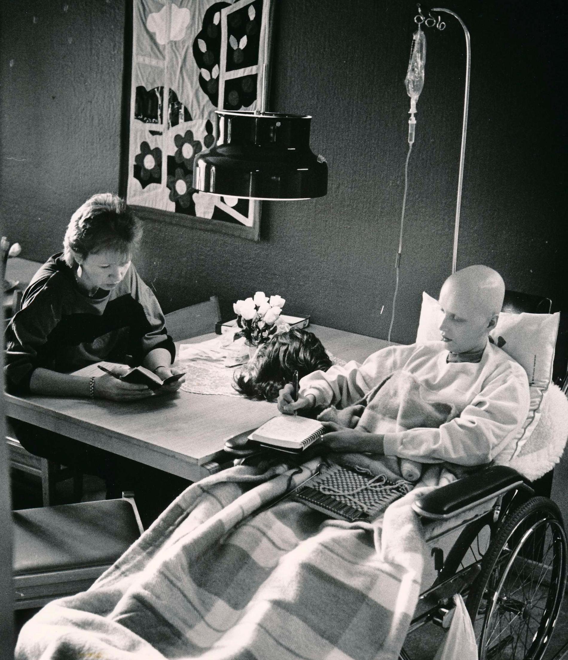 Så såg det ut i dagrummet, en typisk dag 1987 i väntan på cytostatikabehandling. Anita och Annika skriver i sina dagböcker.
