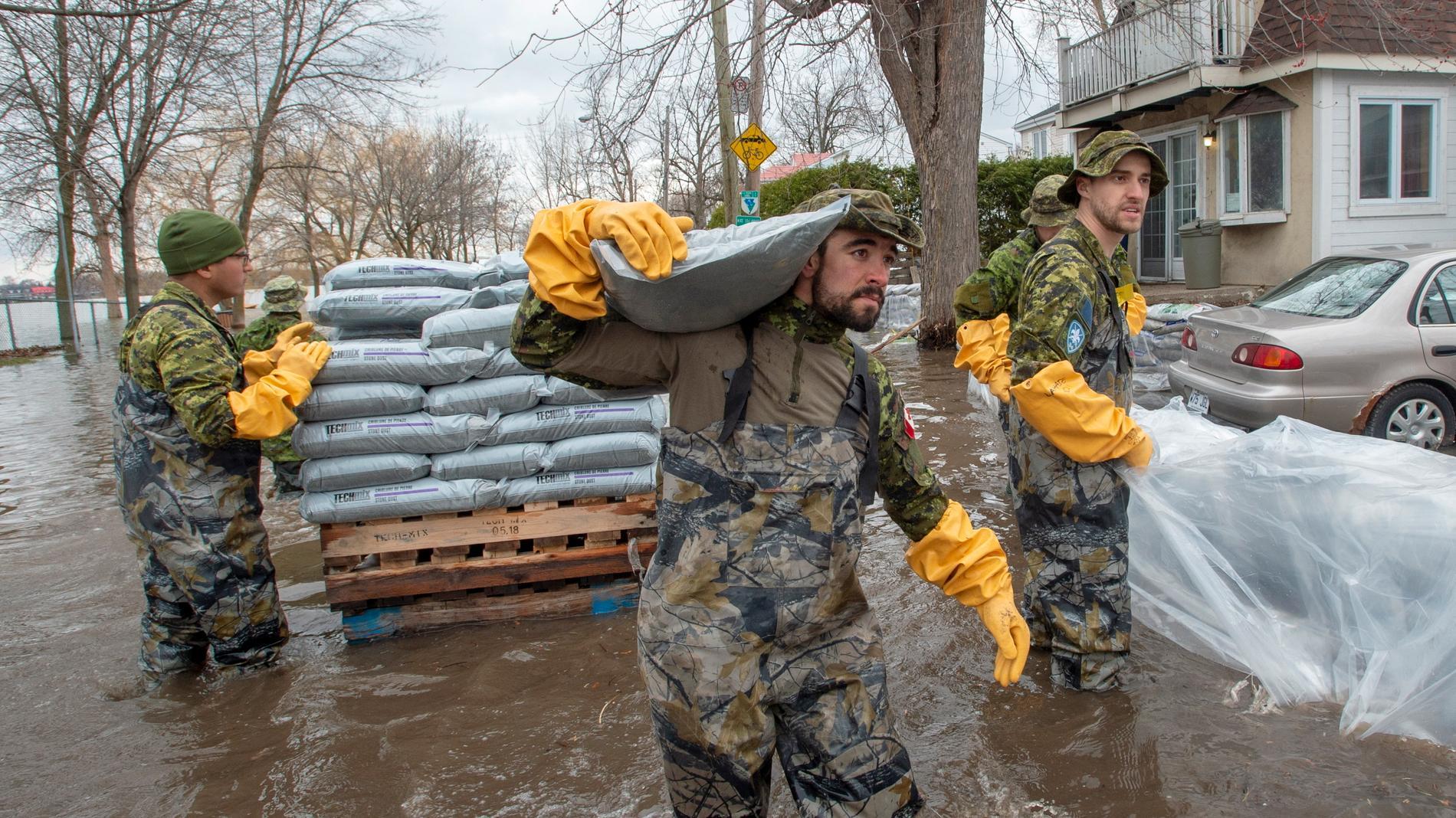 Kanadensiska soldater bär sandsäckar mot översvämningar i Laval, Quebec.
