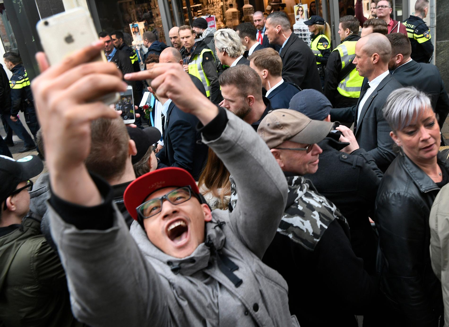 En man tar en selfie och visar fingret samtiodigt som Geert Wilders går förbi.