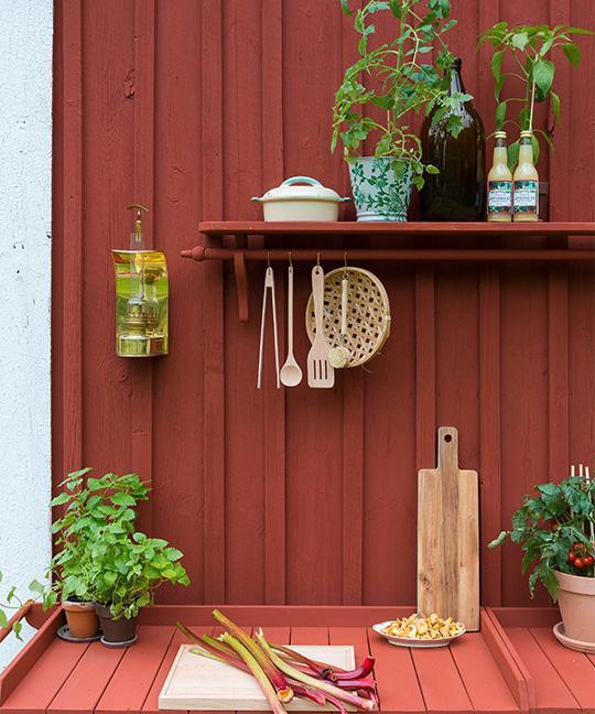 Vid ena kortändan har Sten gjort ett utekök av två planteringsbord från Coop som han målat i Falu rödfärg. Vägghylla och fotogenlykta loppis, hängande träredskap TGR, skärbräda, diskborste och hängande korg Ica Maxi. Grönmönstrad kruka Simply Scandinavia.