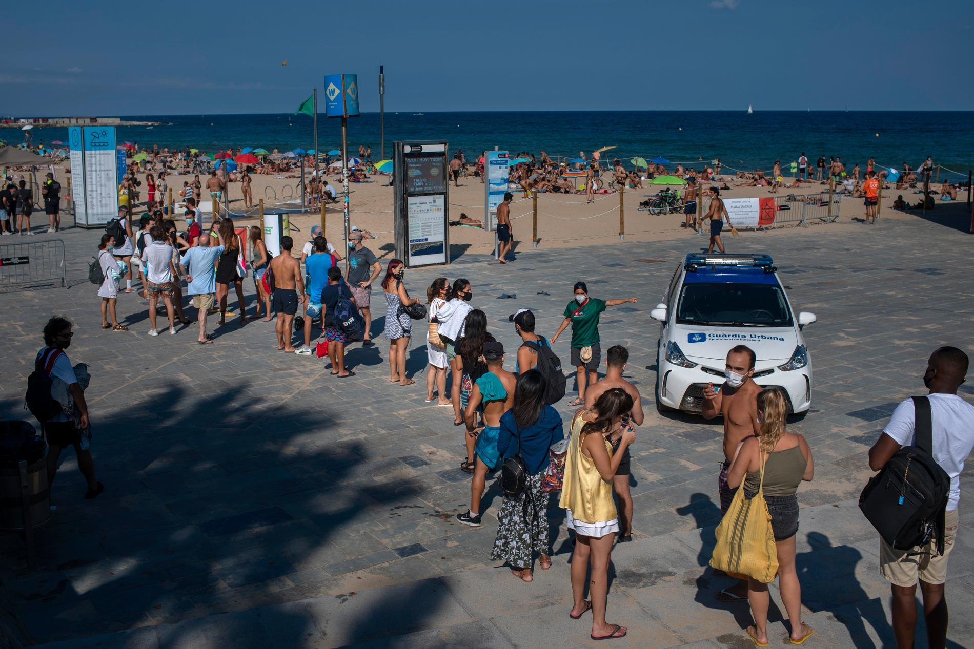 Semesterfirare köar till en strand i Barcelona som stängts av polis på grund av trängsel den 18 juli.