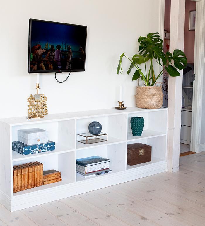 Snyggt inrett på teveväggen. Korg med palm, bägge från Ikea. Ljusstake och mässings - tavla från Hilke Collection. Blå rund vas från Kähler.