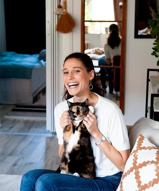 Myriam Jabert i sitt vardagsrum tillsammans med katten Athena. Spegeln i bakgrunden är ett loppisfynd.