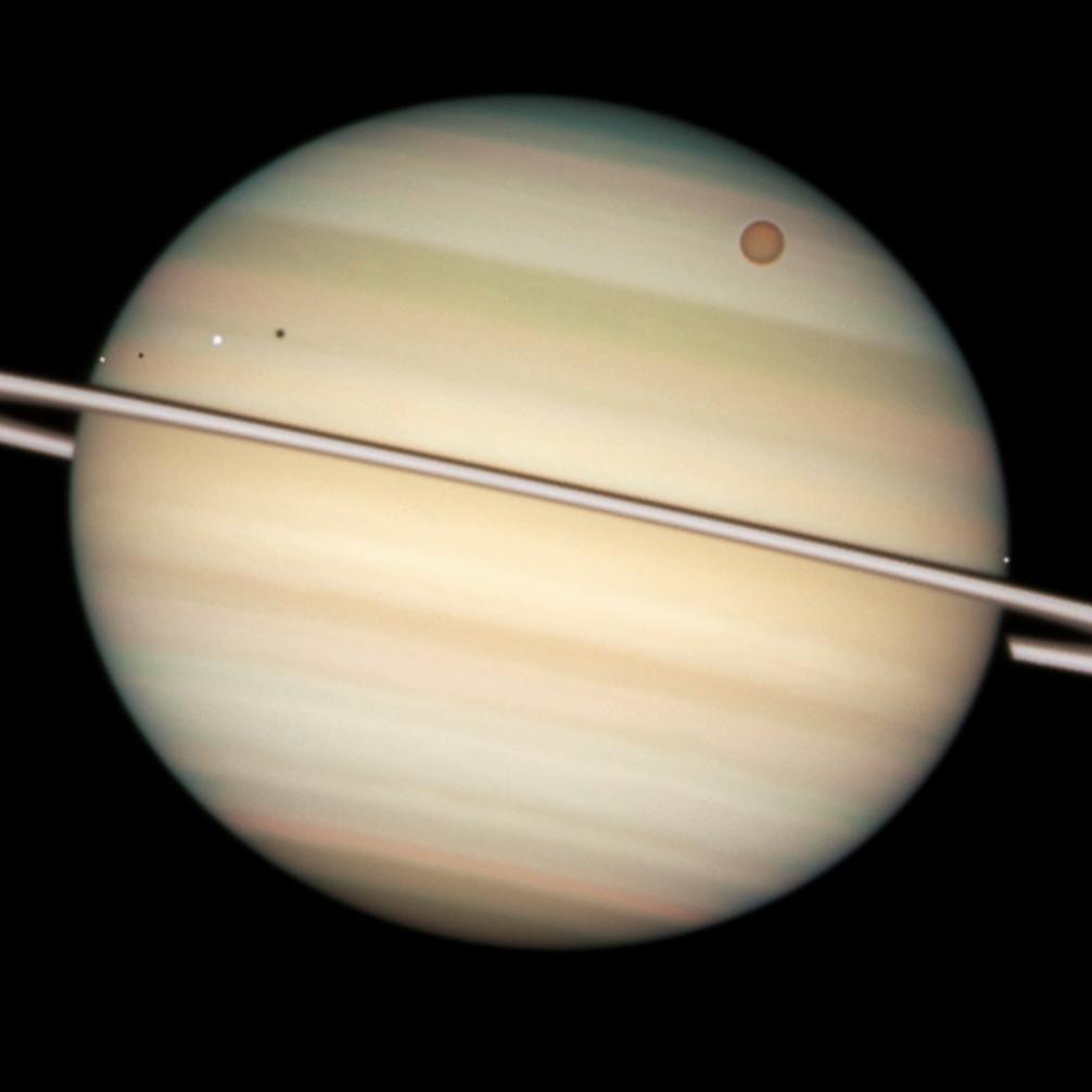På denna bild tagen av Hubble-teleskopet syns flera av Saturnus månar passera framför den i bild. Den största, Titan, är större än planeten Merkurius. Arkivbild från 2009.
