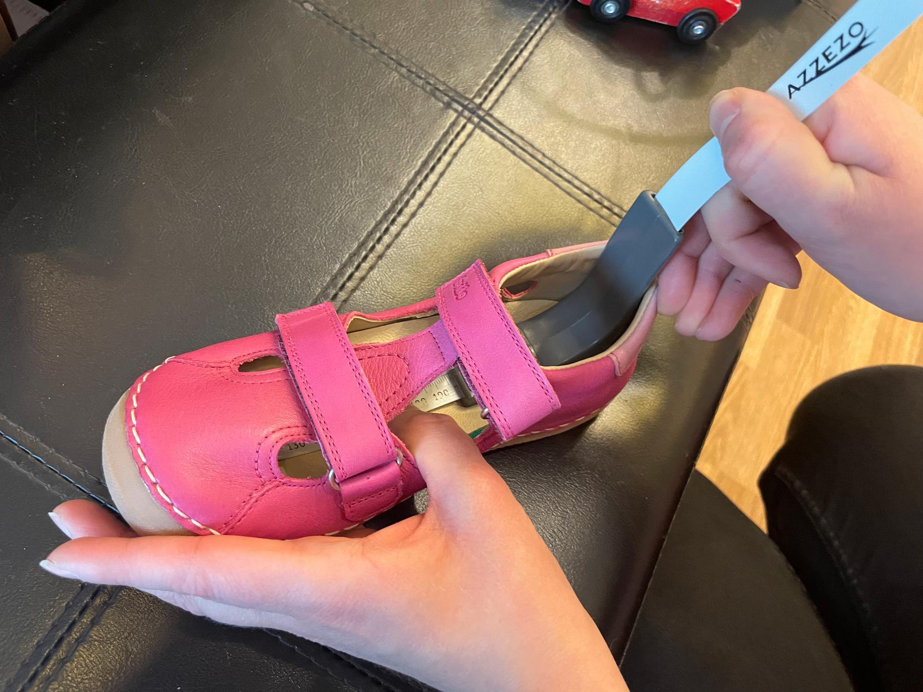 """Tatjana Bebesi visar hur man mäter innermåttet på en barnsko med en mätsticka: """"För att ha ett korrekt resultat placera mätstickan i skon och håll den fast bak mot hälen.Mätstickan ska följa inläggssulan på samma linje som foten följer inuti skon. Kontrollera resultatet medan mätstickan finns kvar i skon. Om mätstickan inte följer linje av foten kan resultatet vara felaktig""""."""