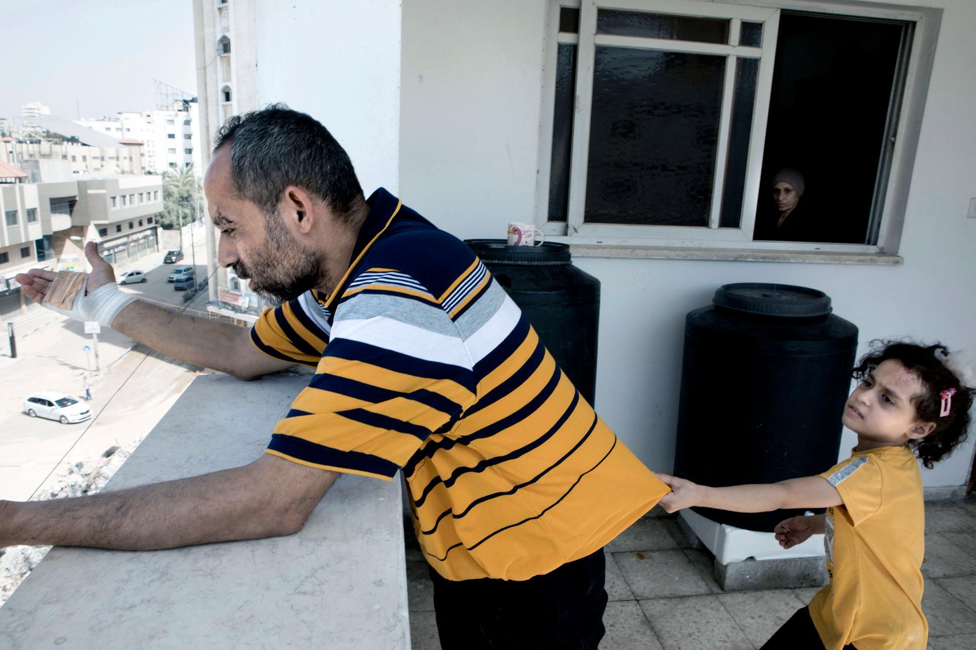 Souzey, 7, tillsammans med pappa Raued, 43, var de enda i familjen som överlevde. På bilden tittar pappa Raued ner på resterna av byggnaden de var i när bomben föll.