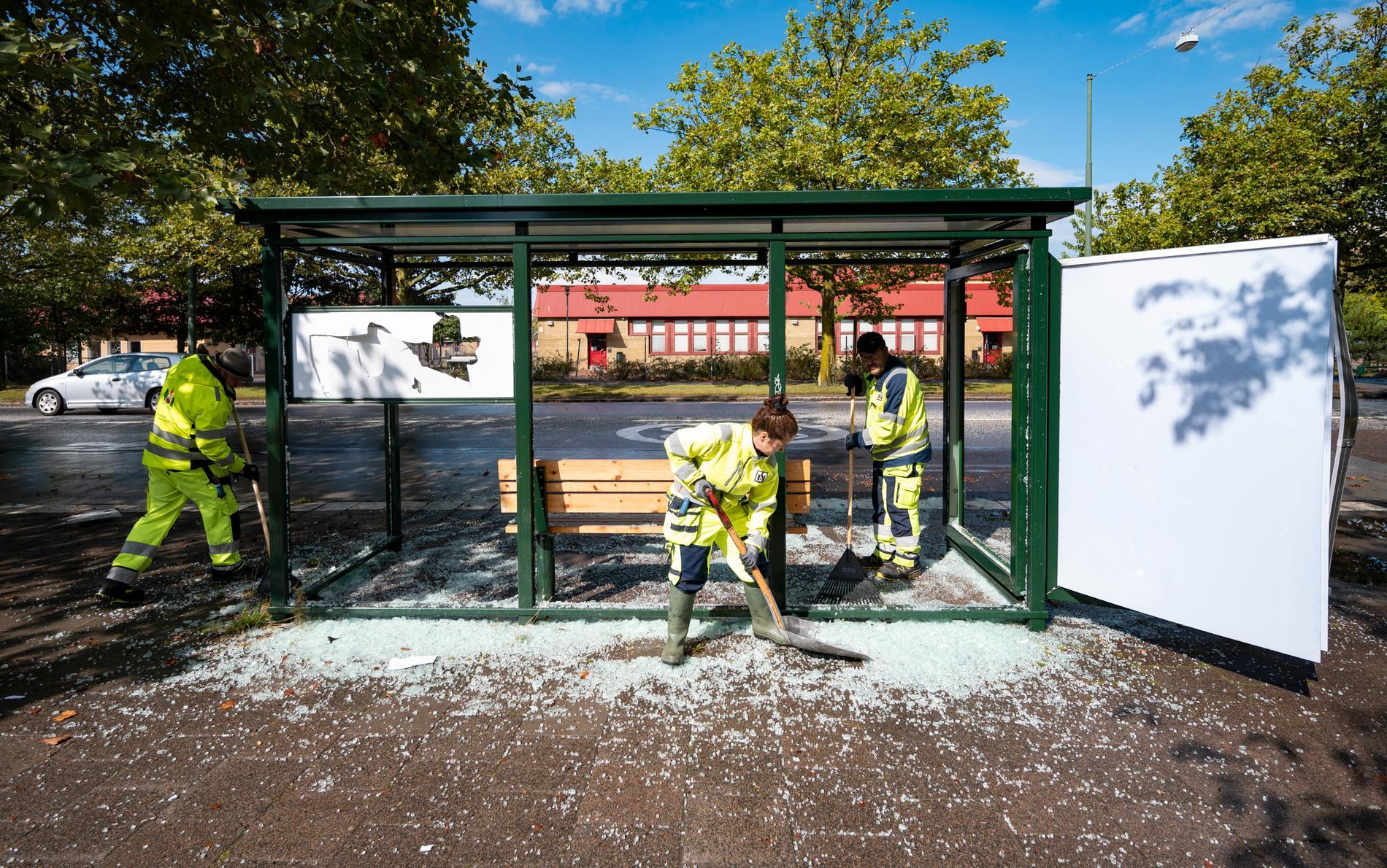 Personal från Malmö Stad röjer upp krossat glas från en av ett 15-tal krossade busskurer på Rosengård i Malmö lördagen efter protesterna.
