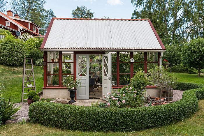 Växthuset ramas in av låga ligusterhäckar i böljande former. Det ger lite rumskänsla och skapar samtidigt naturliga sittplatser i olika väderstreck så att man kan följa solens vandring över tomten.