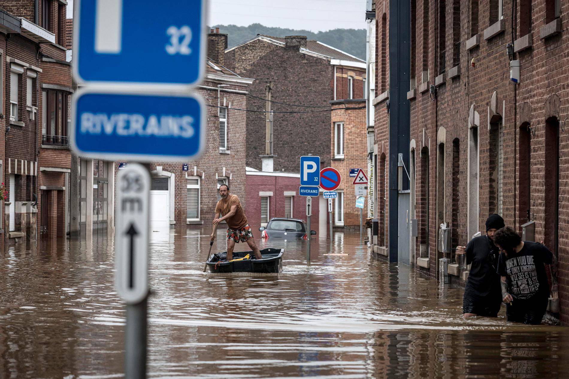 En man ror längs en översvämmad gata i Liègestaden Angleur den 16 juli.