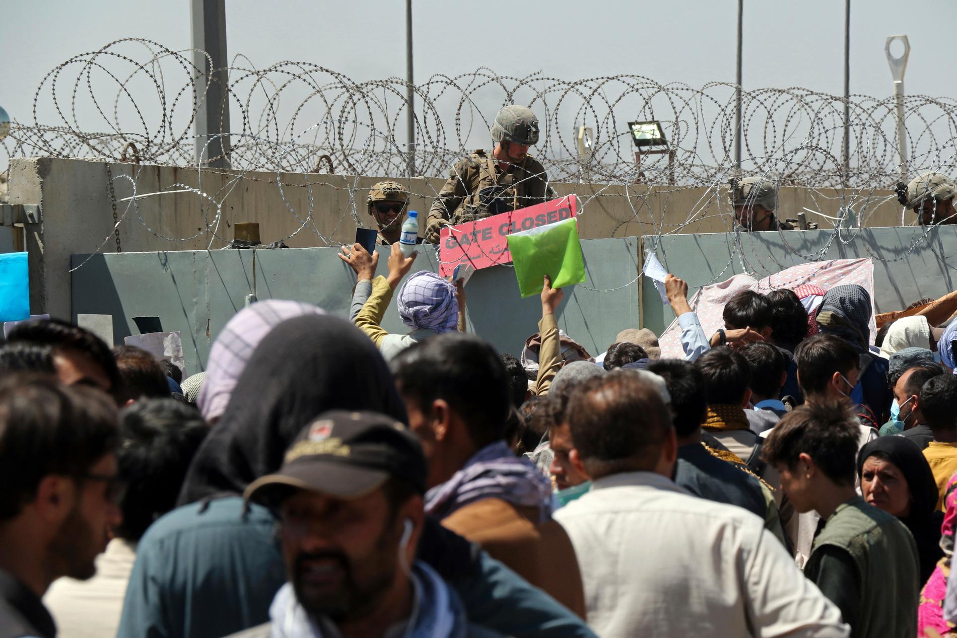 """Bild från Hamid Karzai internationella flygplats i Kabul tidigare idag. En amerikansk soldat håller upp en skylt mot de hundratals människor som samlats vid flygplatsens check-points, med hopp om att evakueras. Redan igår varnade flera länder för att en attack kunde komma på Kabuls flygplats, där tusentals personer befinner sig. I förmiddags gick Storbritannien ut och varnade för att en attack kunde komma """"inom några timmar""""."""